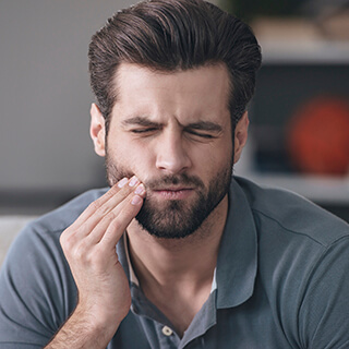 Man in pain holding cheek